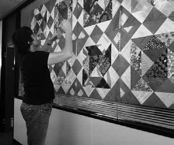 Paull McKee hangs the quilt made from copies of class rolls as part of Information Awareness Month celebrations